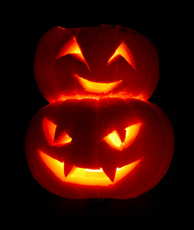 Illuminated cute halloween pumpkins isolated on black background photo