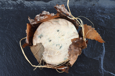 molded: Banon cheese wrapped with leaves on black stone plate
