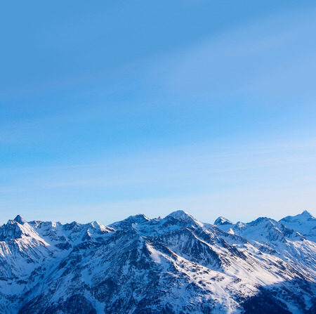 Tops of winter alp mountains at sunny day photo