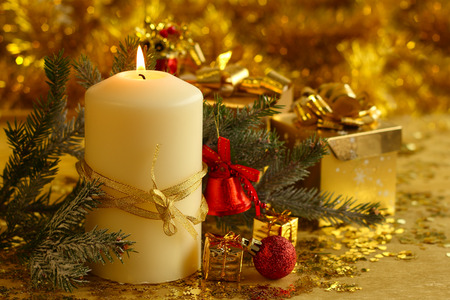Christmas decorative burning candle, fir branch and decor over golden bokeh background photo