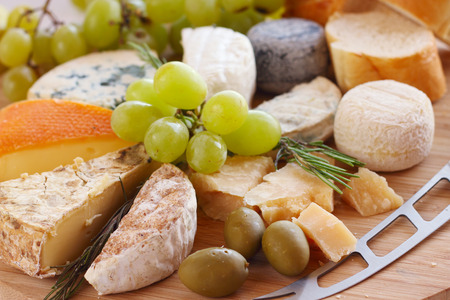 Various types of cheese and knife on wooden board photo