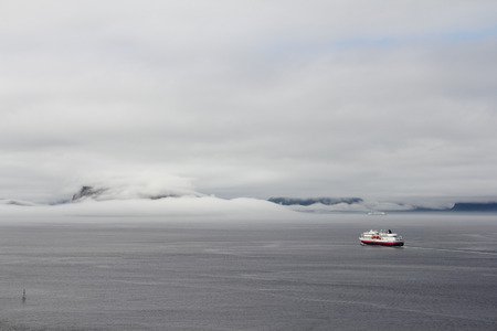 Morning fjord landscape with mountains and fog over water and ship photo