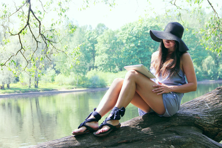 Young woman using tablet outdoor sitting on tree near lake photo