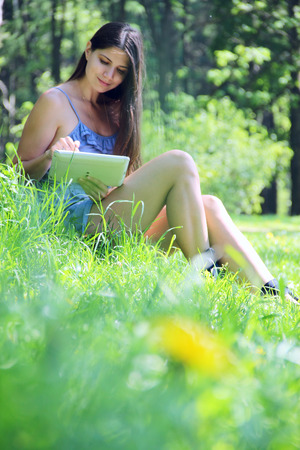 Young woman using tablet outdoor sitting green grass with flowers photo