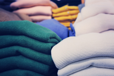 Stacks of clothes in store, close up view photo
