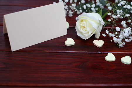 White rose, card and hearts on dark wooden background, Valentines day concept photo