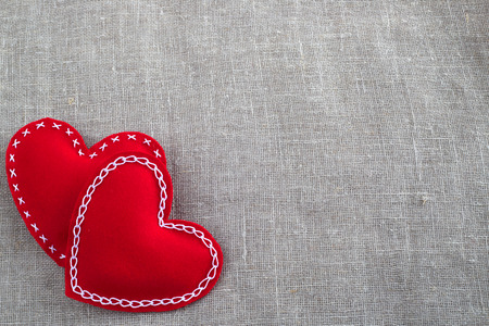Red Valentines day decorative fabric hearts on gray textile background with copy space photo