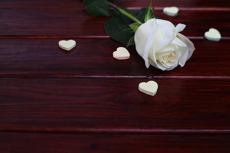 White rose and hearts on dark wooden background, Valentines day concept photo