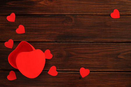 Heart shaped red box and paper hearts for valentines day gift on dark wooden table, top view Stock Photo