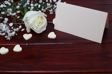 White rose, card and hearts on dark wooden background, Valentines day concept