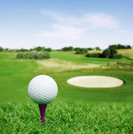Golf ball on course with beautiful blurry landscape on background photo