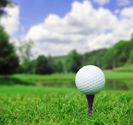 golf clubs: Golf ball on course with beautiful blurry landscape on background