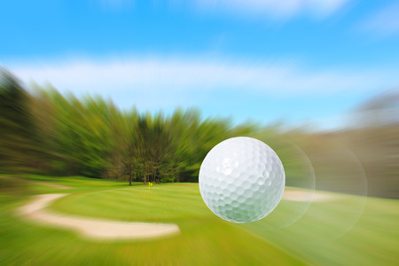 golf field: Close-up of flying golf ball over blurred course Stock Photo