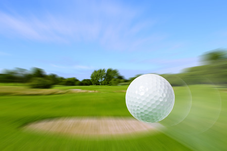 Close-up of flying golf ball over blurred course Stock Photo