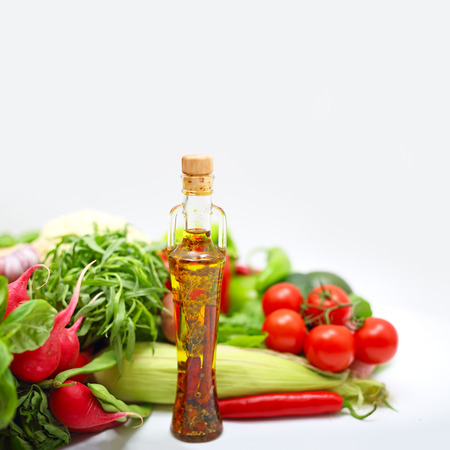 cooking oil: Pile of assorted vegetables and cooking oil on white background