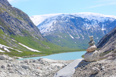 jostedalsbreen: Stack of rocks with mountain and fjord view in Jostedalsbreen National Park, Briksdalen valley, Norway Stock Photo