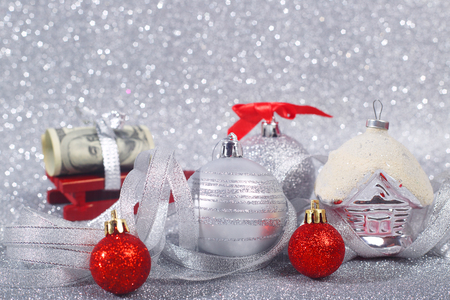 Beautiful red and silver christmas balls and money gift on glitter background with copy space