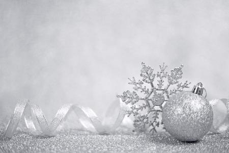 복사 공간 빛나는 반짝이 배경에 실버 크리스마스 공 및 눈송이