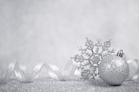 Silver christmas balls and snowflakes on shining glitter background with copy space