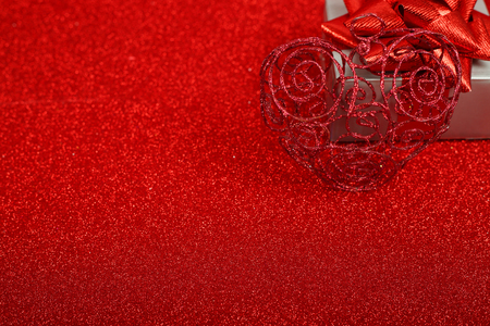 shiny background: Gift Box with heart decor over shiny red glitter background