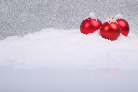 christmas balls: Christmas decorative red balls on snow on glitter background