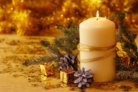 candela: Natale burning decorative candela, filiale di abete e decorazioni su sfondo dorato bokeh