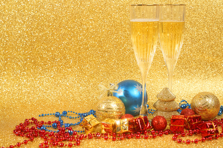 new year eve beads: Champagne and christmas decor on golden glitter background with copy space