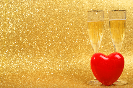 alcohol drinks: Two glasses of champagne and red heart with golden glitter lights on background