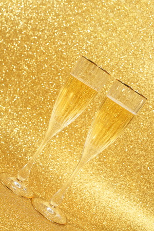 gold flute: Two glasses of champagne with golden glitter lights on background Stock Photo