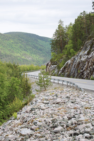 nasty: View on mountain road, rocks and forest at nasty summer day