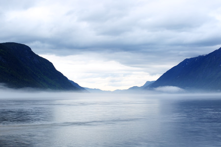 Morning norwegian landscape with mountains and mist over the lake Reklamní fotografie