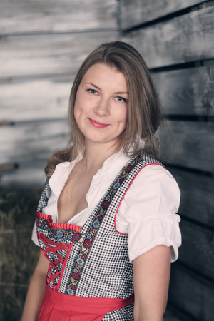 cute young farm girl: Beautiful woman in traditional german dress on hay