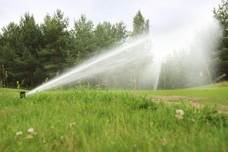 sprinklers: Sprinklers of automatic watering at golf course close up