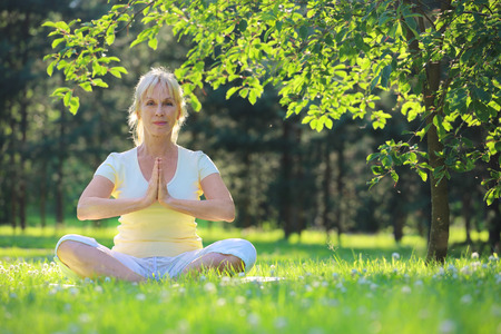 Beautiful mature woman in lotus yoga position in summer park Stock Photo