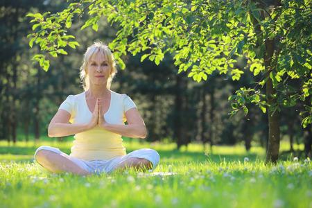 Beautiful mature woman in lotus yoga position in summer park Reklamní fotografie