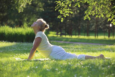 Beautiful mature woman practice yoga in summer park Reklamní fotografie