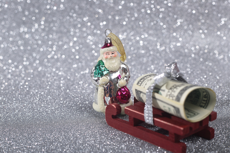 brings: Santa Claus brings money on his sledge on glitter background