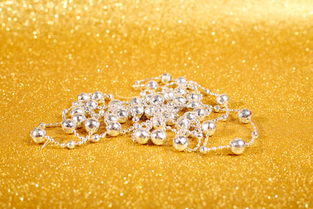 christmas beads: Silver decorative christmas beads on golden glitter background with copy space