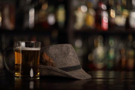 bartend: Oktoberfest beer in glass mug and german hat in bar Stock Photo