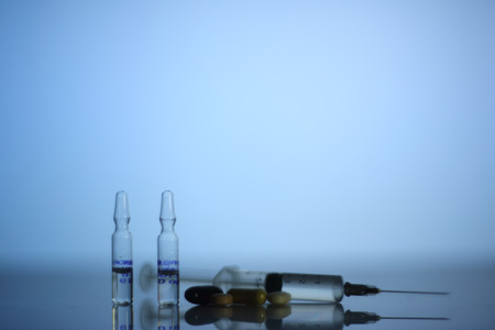 reanimation: Syringe, ampoules and pills on glowing blue reanimation light background