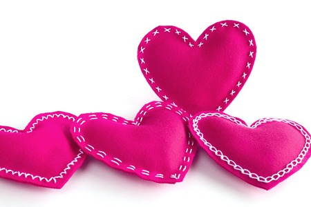 Pink fabric handmade Valentines day hearts isolated on white background