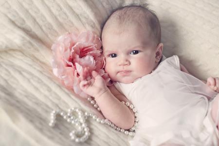 花とパールビーズのファッショナブルなドレスで生まれたばかりの赤ちゃんの女の子