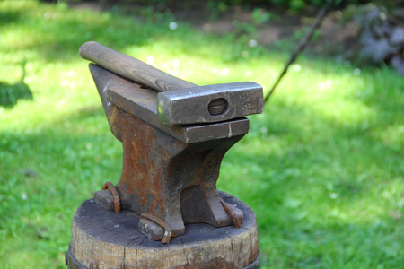 Hammer on blacksmith anvil on green grass background
