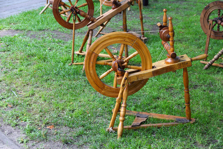 wheel spin: Old traditional wooden spinning wheel on grass at fair
