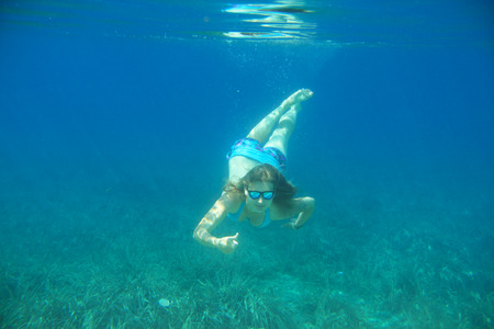 freediving: Woman swimming underwater in blue transparent sea water