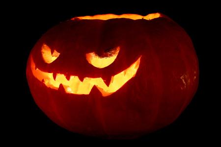 Verlichte leuke die Halloween-pompoen op zwarte achtergrond wordt geïsoleerd