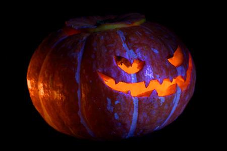 Illuminated cute halloween pumpkin isolated on black background Stock Photo