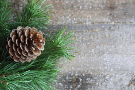 Christmas card, pine cone and branch on wooden background with snow. View with copy space Stock Photo