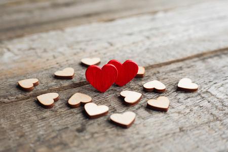 True love concept, Small red hearts surrounded with other hearts on wooden background with copy space