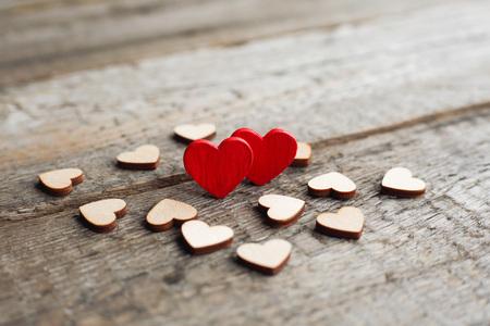 Waar liefdeconcept, Kleine rode harten die met andere harten op houten achtergrond met exemplaarruimte worden omringd